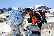 """Tijdens de eerste 2 weken van Augustus werd op een gletsjer in het Kaunertal, hoog in de bergen van Tirol, een Mars simulatie missie uitgevoerd onder de noemer AMADEE-15. Vijf speciaal getrainde """"astronauten"""" uit verschillende Europese landen hezen zich om beurten in de twee beschikbare ruimtepakken om o.a. geologische en astrobiologische experimenten uit te voeren, nieuwe technieken uit te testen en in het algemeen kennis en ervaring op te doen voor toekomstige echte bemande missies naar Mars. De missie werd georganiseerd door het Oostenrijkse ruimtevaartgenootschap ÖWF (Österreichisches Weltraum Forum), een verbond van professionals in de ruimtevaartindustrie, wetenschappers en mensen met een passie voor de ruimtevaart. Foto: De Spaanse astronaut Iñigo Muñoz Elorza tijdens de perspresentatie op dag 2. Leden van het support team moeten hun communicatie met de astronauten voeren via het missie controlecentrum of anders heel hard roepen tegen de helm. COPYRIGHT JURRIAAN BROBBEL"""