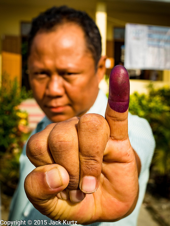 08 NOVEMBER 2015 - YANGON, MYANMAR: A man displays displays his pinkie finger, stained with ink, a sign that he voted in North Okkalapa, a township outside of Yangon center Sunday. The citizens of Myanmar went to the polls Sunday to vote in the most democratic elections since 1990. The National League for Democracy, (NLD) the party of Aung San Suu Kyi is widely expected to get the most votes in the election, but it is not certain if they will get enough votes to secure an outright victory. The polls opened at 6AM. In Yangon, some voters started lining up at 4AM and lines were reported to long in many polling stations in Myanmar's largest city.      PHOTO BY JACK KURTZ