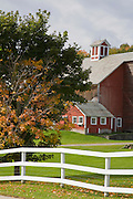 Old barn and silo in Fall with white fence.