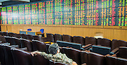 02 SEPTEMBER 2013 - BANGKOK, THAILAND:  A woman watches real time changes in the Thai stock market on the stock ticker at Asia Plus Securities headquarters in central Bangkok. The Thai stock market has declined more than 20% from its 2013 high as data as Thailand entered a recession in the second quarter. The loss of value in the Stock Exchange of Thailand (SET) is the greatest sell off since the end of the Asian financial crisis in 1998. Foreign investors have sold more than $1 billion of local shares this month amid signs of slowing regional economic growth and speculation that the U.S. Federal Reserve will soon cut its stimulus.     PHOTO BY JACK KURTZ