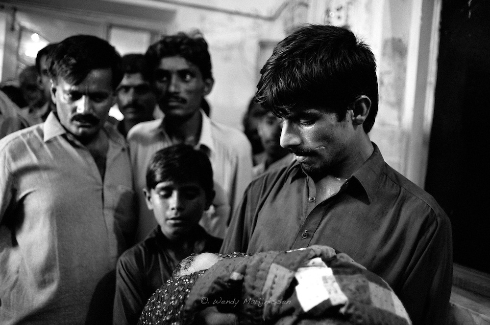 Rabia's husband of 19 Makhoul looks at his newborn baby boy for the first time. Thari Mirwah, Pakistan, 2010