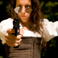 Young woman holding a 9mm gun pointing at camera