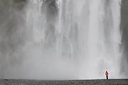 Touristin before the big waterfall of Skogarfoss. Iceland.