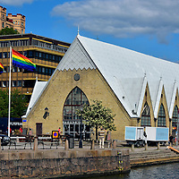 Feskek&ocirc;rka Fish Market in Gothenburg, Sweden <br /> Based on its location in Western Sweden along the shores of the Kattegat bay which connects to the North Sea, Gothenburg had a prosperous and growing fishing trade through the mid 18th century.  But its fish markets were often unregulated, smelly and guilty of unsanitary conditions. In response, the Feskek&ocirc;rka was built in 1874 along the Rosenlund Canal as an indoor seafood market.  It still has stalls and restaurants that serve a variety of delicious fish, most of which are freshly caught from the Baltic Sea.