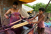 The owner of a house transformed into a small-scale workshop in the slum surrounding Firozabad, renowned as the 'glass city', in  Uttar Pradesh, northern India, is painting bundles of bracelets while a local boy is assisting him. Due to extreme poverty, over 20.000 young children are employed to complete the bracelets produced in the industrial units. This area is considered to be one of the highest concentrations of child labour on the planet. Forced to work to support their disadvantaged families, children as young as five are paid between 30-40 Indian Rupees (approx. 0.50 EUR) for eight or more hours of work daily. Most of these children are not able to receive an education and are easily prey of the labour-poverty cycle which has already enslaved their families to a life of exploitation. Children have to sit in crouched positions, use solvents, glues, kerosene and various other dangerous materials while breathing toxic fumes and spending most time of the day in dark, harmful environments. As for India's Child Labour Act of 1986, children under 14 are banned from working in industries deemed 'hazardous' but the rules are widely flouted, and prosecutions, when they happen at all, get bogged down in courts for lengthy periods. A ban on child labour without creating alternative opportunities for the local population is the central problem to the Indian Government's approach to the social issue affecting over 50 million children nationwide.