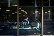 A corporate office worker has the Union jack flag attached to his desk in the City of London.