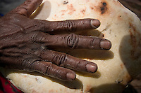 The lined hands of aboriginal Wik elder Hersey Yunkaporta as she kneads home-made damper, or bread in the heart of the Aurukun Wetlands, remote Cape York, far northern Queensland, Australia.