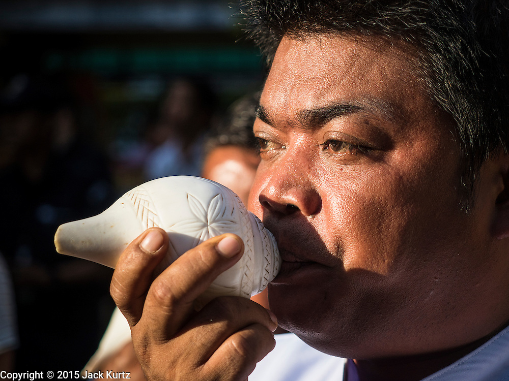 "04 SEPTEMBER 2015 - BANGKOK, THAILAND: An attendant to the Brahman priests blows a conch shell during a blessing ceremony in front of the Erawan Shrine Friday. A ""Holy Religious Ceremony for Wellness and Prosperity of our Nation and Thai People"" was held Friday morning at Erawan Shrine. The ceremony was to regain confidence of the Thai people and foreign visitors, to preserve Thai religious customs and traditions and to promote peace and happiness inThailand. Repairs to Erawan Shrine were completed Thursday, Sept 3 after the shrine was bombed on August 17. Twenty people were killed in the bombing and more than 100 injured. The statue of the Four Faced Brahma in the shrine was damaged by shrapnel and a building at the shrine was damaged by debris.     PHOTO BY JACK KURTZ"