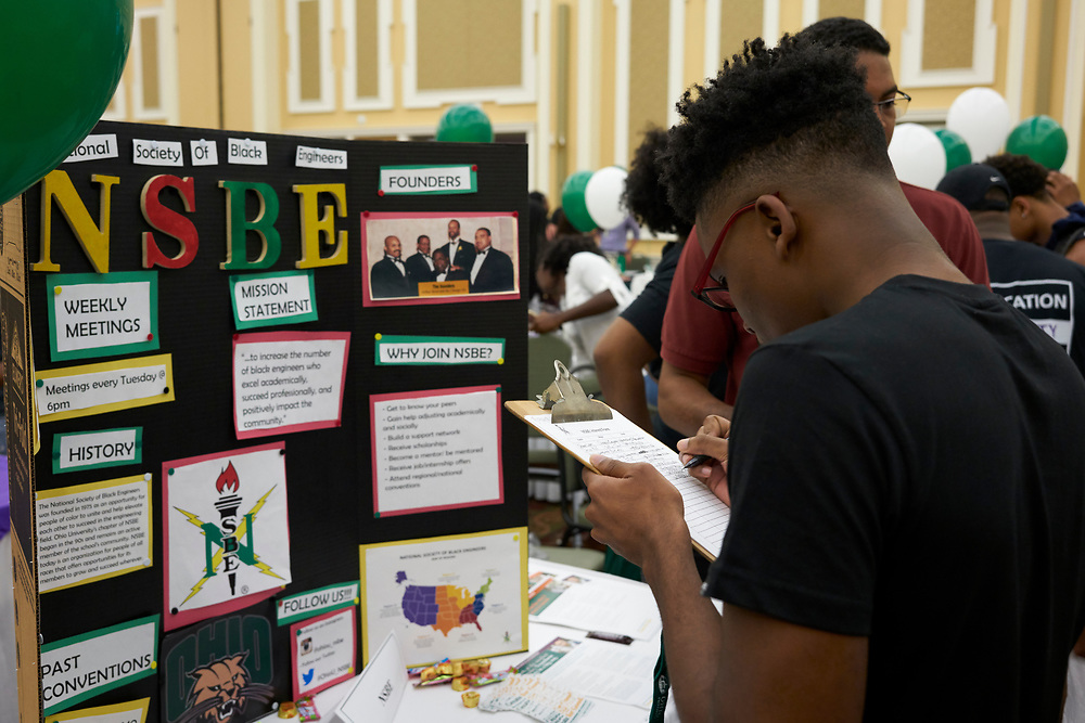 A student signs up for National Society of Black Engineers.