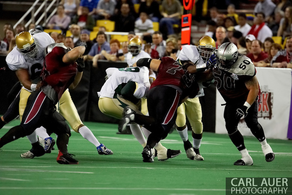 4/12/2007 - Dustin Almond (9) gets sacked by the defensive line led by Lokeni Lokeni, Jr. (75) of the Alaska Wild  in the first professional football game in Alaska.