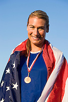 Female athlete wrapped in american flag with golden medal on neck