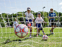 Saba and Michael work on drills with Coach Attie in the Micro Stars division of the On Goal Soccer Camp with the Evangelical Baptist Church at Leavitt Park Thursday morning.  (Karen Bobotas/for the Laconia Daily Sun)