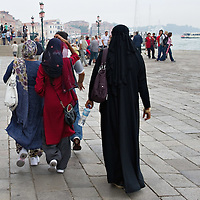"VENICE, ITALY - JUNE 01:  Women wearing veils and burqua walks just few yards away of Flavio Lucchini's  exhibition ""What Women Want (?)"" on June 1, 2011 in Venice, Italy. The exhibition addresses the controversiat theme of the burqa  (Photo by Marco Secchi/Getty Images)"
