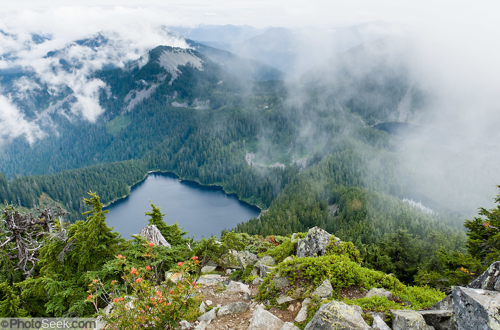 """A partly cloudy view reveals Lake Kulla Kulla and distant peaks seen from Mount Defiance, a side hike from the Mason Lake Trail (also known as """"Ira Spring Memorial Trail"""") near Interstate 90, Alpine Lakes Wilderness Area (Mount Baker Snoqualmie National Forest), Washington, USA."""