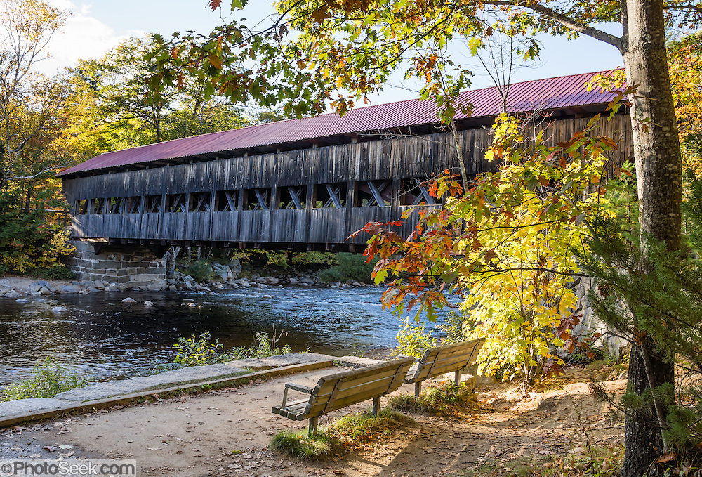 "Albany Covered Bridge was built in 1858 and renovated in 1970 in the town of Albany in White Mountain National Forest, New Hampshire, USA. Albany Covered Bridge spans the Swift River along Passaconaway Road just east of Kancamagus Highway (NH Route 112), six miles west of Conway. Come around the first week of October to enjoy leaf peeping during the peak of autumn foliage colors. In order to reach Covered Bridge Campground, the 7' 9"" height restriction of Albany Covered Bridge requires larger RVs to loop around via Conway on Kancamagus Highway (NH Route 112), go left (east) on H113, go left (north) on Washington Street, fork left on West Side Road, then go left (west) on Passaconaway Road for six miles to the nice National Forest campground near the covered bridge. The White Mountains (a range in the northern Appalachian Mountains) cover a quarter of the state of New Hampshire."
