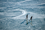 Two ice skaters glide across the frozen surface of Slide Lake on Saturday, enjoying a rare combination of cold, sunny weather and no snow on the lake.