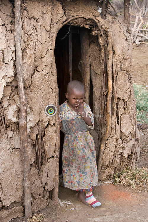Maasai young girl, at home,  in Kenya. The Maasai are an indigenous African ethnic group of semi-nomadic people / Menina Masai no Quenia, na porta de sua casa. Os Masai formam um grupo etnico africano de seminomades.