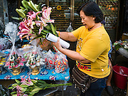 "21 DECEMBER 2015 - BANGKOK, THAILAND:  A woman shops for floral arrangements from street vendors in Pak Khlong Talat, also called the Flower Market. The market has been a Bangkok landmark for more than 50 years and is the largest wholesale flower market in Bangkok. A recent renovation resulted in many stalls being closed to make room for chain restaurants to attract tourists. Now Bangkok city officials are threatening to evict sidewalk vendors who line the outside of the market. Evicting the sidewalk vendors is a part of a citywide effort to ""clean up"" Bangkok.      PHOTO BY JACK KURTZ"