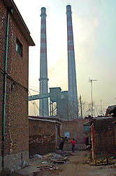 China, Taiyuan, 2008. Taiyuan Iron and Steel's smokestacks dominate the scene on a cold winter day. Factory workers reside in and around the plant.