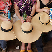 Race fans rest their hats on their laps as they take cover from the sun between races at the 138th running of the Kentucky Derby at Churchill Downs in Louisville, Ky. Saturday May 5, 2012.  Photo by David Stephenson