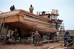 A crew of workers build a wooden fishing boat in Callao, the main port of Peru.