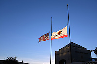 Expressing what most people feel about Friday's attacks in Paris, flags fly at half-mast in the setting sun in Salinas.