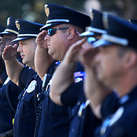 Starkville police officers salute the American flag as it is raised by the Starkville Police Department Honor Guard at the start of the grand opening ceremony of the renovated police headquarters on Friday morning in Starkville.