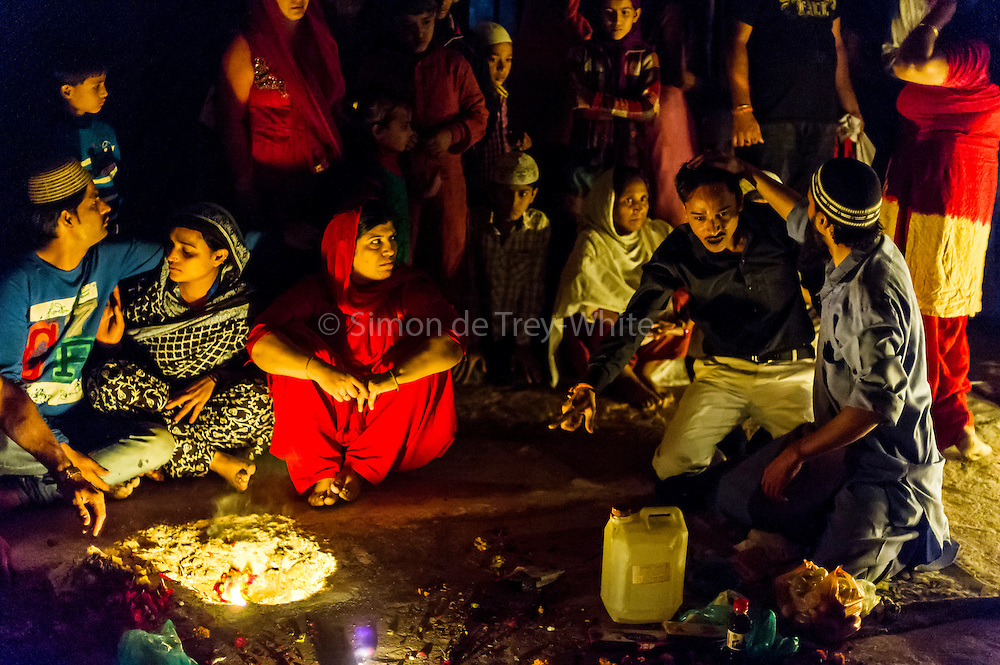 12th November 2015, New Delhi, India. A man receiving the blessings of the divine from a Sufi 'pir' (master) reacts at a shrine dedicated to Djinn worship in the ruins of Feroz Shah Kotla in New Delhi, India on the 12th November 2015<br /> <br /> PHOTOGRAPH BY AND COPYRIGHT OF SIMON DE TREY-WHITE a photographer in delhi<br /> + 91 98103 99809. Email: simon@simondetreywhite.com<br /> <br /> People have been coming to Firoz Shah Kotla to pray to and leave written notes and offerings for Djinns in the hopes of getting wishes granted since the late 1970's. Jinn, jann or djinn are supernatural creatures in Islamic mythology as well as pre-Islamic Arabian mythology. They are mentioned frequently in the Quran  and other Islamic texts and inhabit an unseen world called Djinnestan. In Islamic theology jinn are said to be creatures with free will, made from smokeless fire by Allah as humans were made of clay, among other things. According to the Quran, jinn have free will, and Iblīs abused this freedom in front of Allah by refusing to bow to Adam when Allah ordered angels and jinn to do so. For disobeying Allah, Iblīs was expelled from Paradise and called &quot;Shayṭān&quot; (Satan).They are usually invisible to humans, but humans do appear clearly to jinn, as they can possess them. Like humans, jinn will also be judged on the Day of Judgment and will be sent to Paradise or Hell according to their deeds. Feroz Shah Tughlaq (r. 1351&ndash;88), the Sultan of Delhi, established the fortified city of Ferozabad in 1354, as the new capital of the Delhi Sultanate, and included in it the site of the present Feroz Shah Kotla. Kotla literally means fortress or citadel.