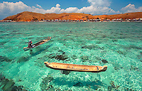 A dugout canoe plies crystal clear waters offshore from bright red Papagaran island, Komodo National Park. Photography by Djuna Iveerigh for RARE Conservation.