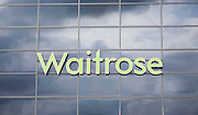 Dark clouds reflected in glass surface of Waitrose store, Ipswich, Suffolk, England