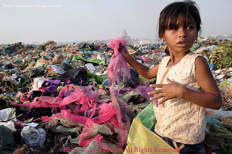 """A young girl who works as a bottle and can collector at The Stung Meanchey Landfill rummages through fabric remnants in Phnom Penh, Cambodia. She contributes to her family's income by scavenging for bottles, cans, and soft clear plastic. The sanitation dump, known as """"Smokey Mountain"""", is a major source of air pollution that impacts the surrounding environment, and is well known for its poor sanitary conditions."""