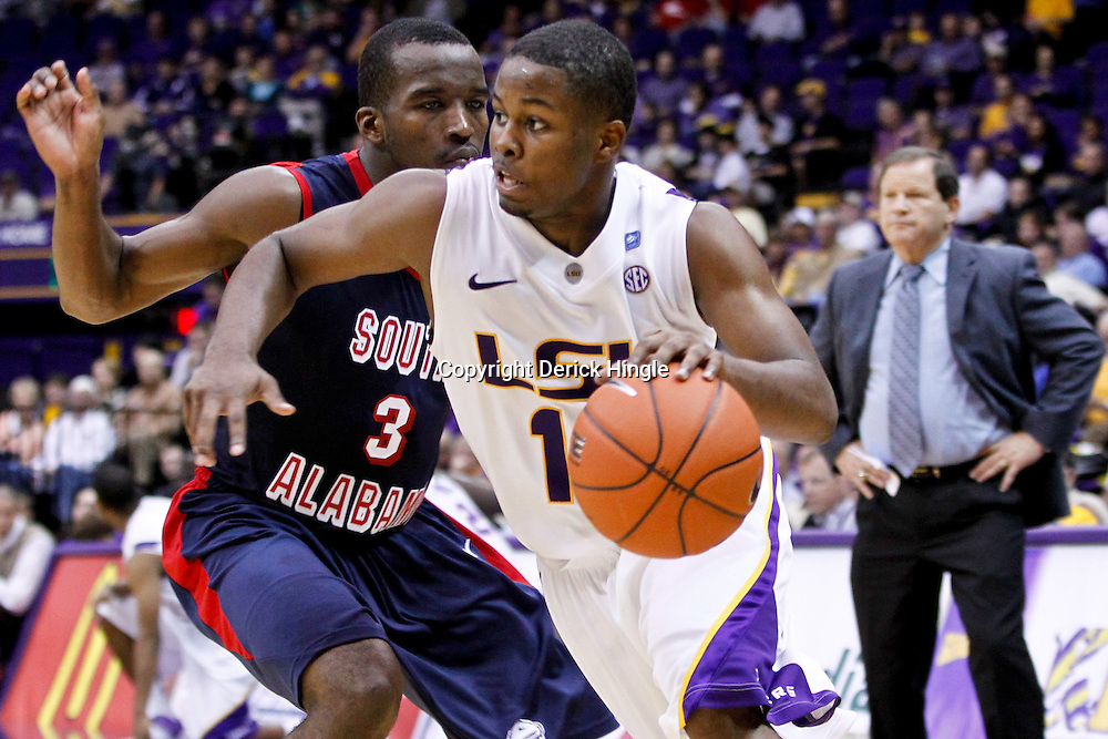 November 23, 2011; Baton Rouge, LA; LSU Tigers guard Andre Stringer (10) drives past South Alabama Jaguars guard Xavier Roberson (3) during the first half of a game at the Pete Maravich Assembly Center.  Mandatory Credit: Derick E. Hingle-US PRESSWIRE