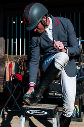 March 22, 2019 - Raeford, North Carolina, US - March 22, 2019 - Raeford, N.C., USA - DOUG PAYNE of the United States puts the finishing touches on his boots before competing in the CCI3-S show jumping division at the sixth annual Cloud 11-Gavilan North LLC Carolina International CCI and Horse Trial, at Carolina Horse Park. The Carolina International CCI and Horse Trial is one of North AmericaÃ•s premier eventing competitions for national and international eventing combinations, hosting International competition at the CCI2*-S through CCI4*-S levels and National levels of Training through Advanced. (Credit Image: © Timothy L. Hale/ZUMA Wire)