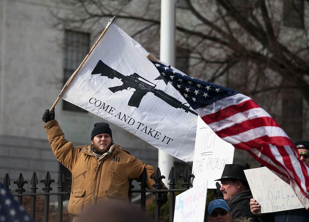 "Boston, MA 01/19/2013.Nick Marchesi of Boston waves a ""Come And Take It"" flag with the image of an AR-15 during Saturday's protest at the Massachusetts State House, part of a coordinated nationwide movement against proposed gun control legislation..Alex Jones / www.alexjonesphoto.com"