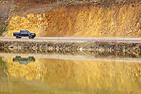 A motorist drives past a colorful, weathered hillside Thursday reflected in the surface of Fernan Lake.