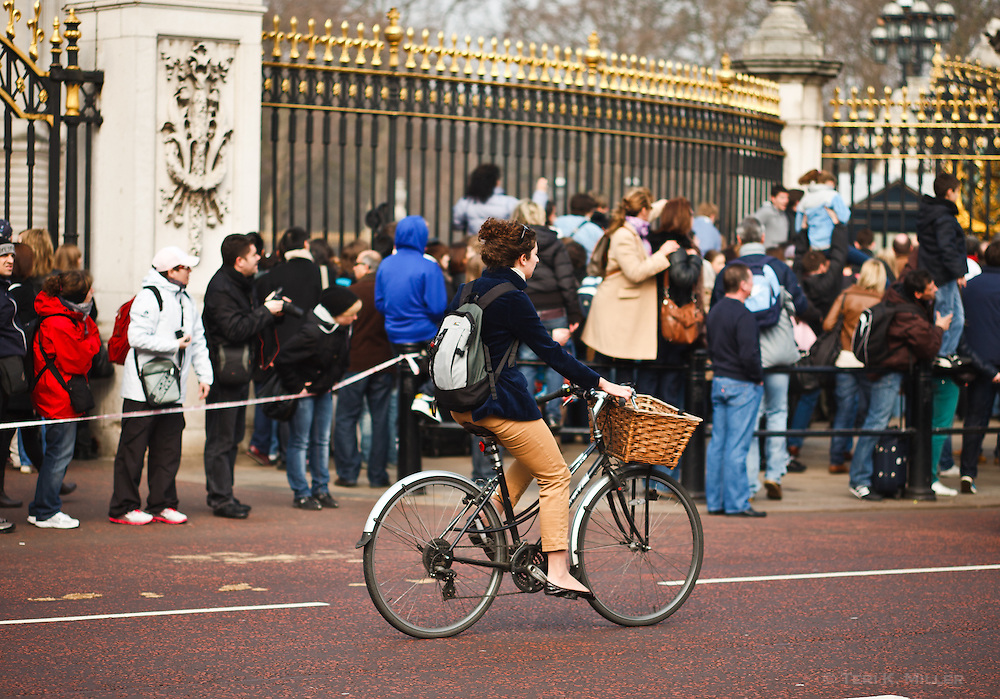 A woman rides a bicycle in front of the crowds at Buckingham Palace, London, England.