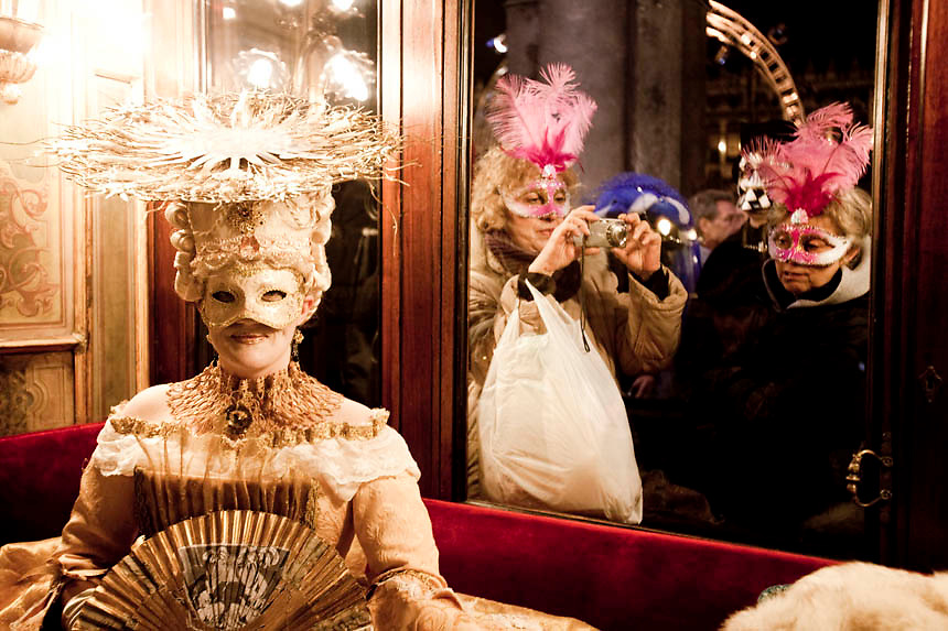 "Masked revellers look into ""Florian Café"" in Saint Mark Square during the first day of Venetian Carnival in Venice."
