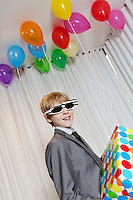 Happy young boy wearing sunglasses holding gift in party