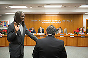 Newly elected Board member Chris Norwood, left, is sworn into office by Pastor Randy Estrada during the Milpitas Unified School District Board of Education Administration of the Oath of Office ceremony at the Board of Education in Milpitas, California, on December 9, 2014. (Stan Olszewski/SOSKIphoto)