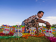 "24 JULY 2014 - BANGKOK, THAILAND: A kite vendor sets up his kites on Sanam Luang during the happiness party. People bought and flew kites during the party. The Thai Junta is organizing a series of public events throughout Thailand meant to bolster public opinion. The events are called ""restoring happiness to the people"" parties. They feature historic pageants, music, food, health checks and free haircuts. The party in Bangkok is on Sanam Luang, the Royal Parade Ground, which is near the Grand Palace and the Ministry of Defense.    PHOTO BY JACK KURTZ"