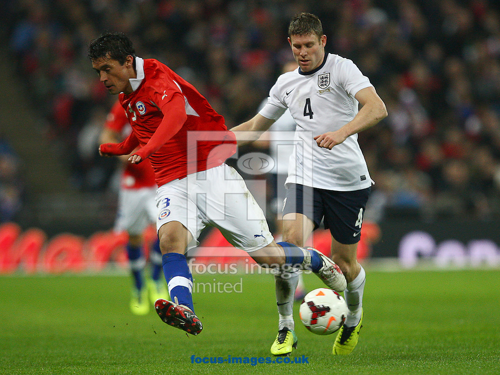 Picture by Rob Fisher/Focus Images Ltd +44 7450 945824<br /> 15/11/2013<br /> James Milner of England and Marcos Gonzalez of Chile during the Friendly match at Wembley Stadium, London.