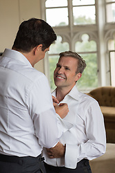 gay man helping his partner dress for their wedding