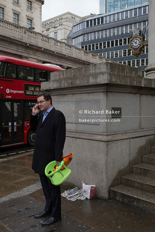 A businessman and father holds a bright green child's seat, on 2nd February 2017, in the City of London, England.