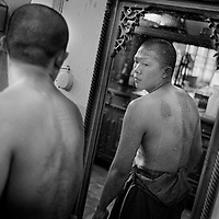 Nakhon Chai Si district, February 2010, Wat Bang Phra Temple. Religious tattoo on the back of a Monk Bouddhist, in Nakhon Chai Si district, Thailand, about 50 km west of Bangkok. The temple is famous for its monks and their practice of giving Sak Yant tattoos with wooden bamboo and metal needless. Many believe that protective energy flows through the tattoos, keeping them safe from harm. It is not simply about getting a talisman tattoo here. The owner must activate it in order for it to serve as a lifesaving conduit. He or she must respect the precepts set by the head master.