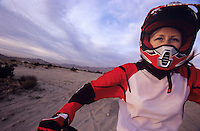 Woman in Racing Gear Riding Motorcycle