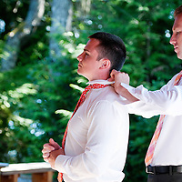A groomsman assists Travis with his tie before his Vancouver Island wedding to Amy.