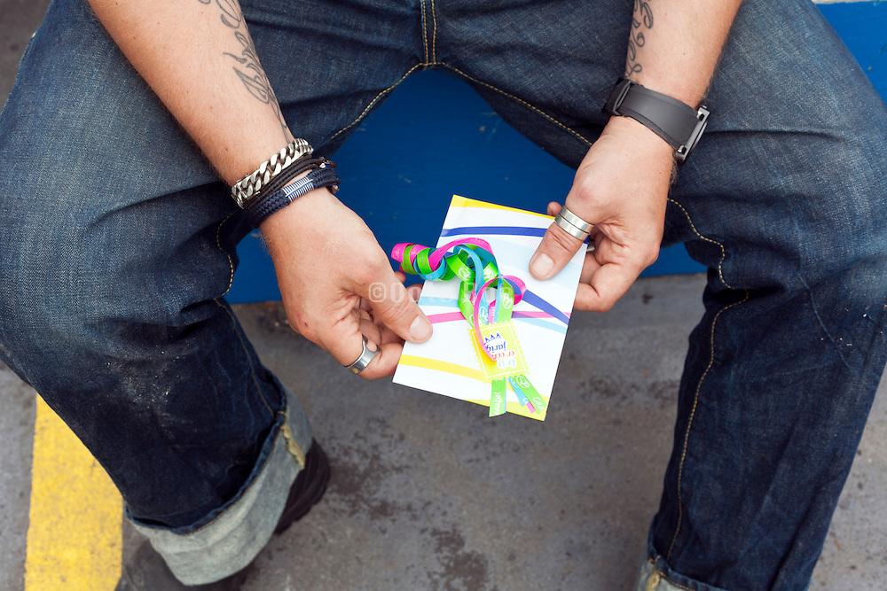 tattooed man with birthday envelope gift