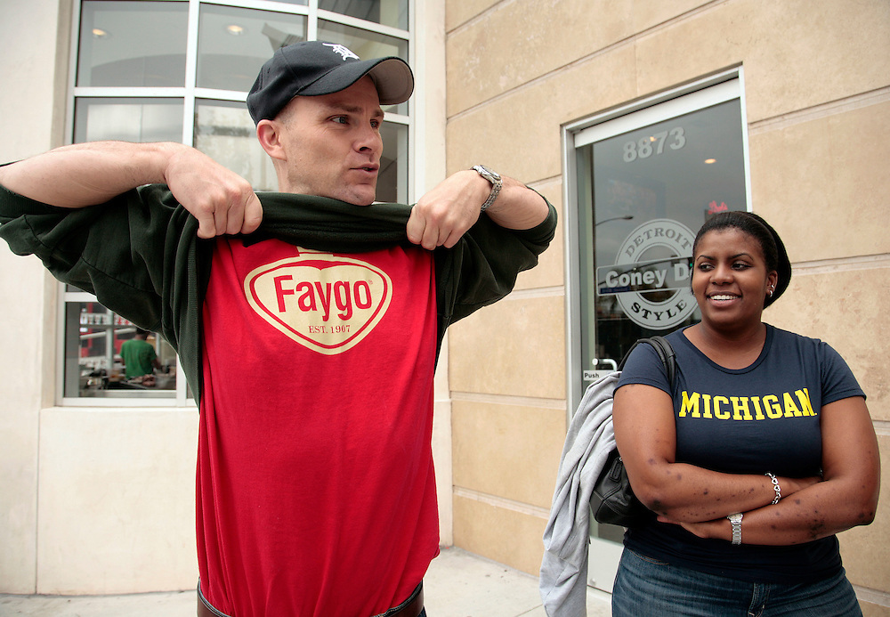 Guy Klender, left, of Burbank, Calif. shows off his Faygo t-shirt as Tiffani Kensler of Los Angeles looks on as the opening of Coney Dog, a Detroit-style Coney Island hot dog restaurant, on Sunset Boulevard in West Hollywood, Calif., Saturday, June 19, 2011. Klender is originally of Hazel Park, Mich. and Kensler of Detroit. (AP Photo/Jason Redmond)