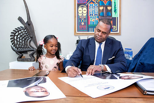 2019 Commencement speaker Kasim Reed seated at a desk surrounded by artwork, signing a poster. His daughter stands at his side.