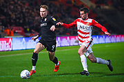 Cauley Woodrow of Barnsley (9) and Matty Blair of Doncaster Rovers (17) in action during the EFL Sky Bet League 1 match between Doncaster Rovers and Barnsley at the Keepmoat Stadium, Doncaster, England on 15 March 2019.